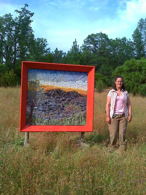 4 ft by 4 ft colored mosaic of a sunset view of Clearlake and Mt Konocti . The Artist Alicia Farnsworth stands beside it in a rural park setting.