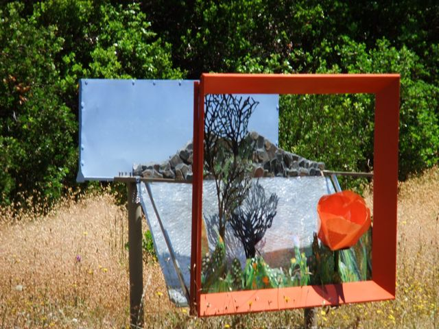 Artist Alicia Lee Farnsworth created this 4 by 6 by 2.5 foot perforated steel  repouse landscape of Clear Lake and mosaic Mt Konoct. It is freestanding in a grassy natural park in Middletown California and has a big international orange wooden picture frame. Part of the 2010 Lake County Ecoarts 10 Sculpturewalk.